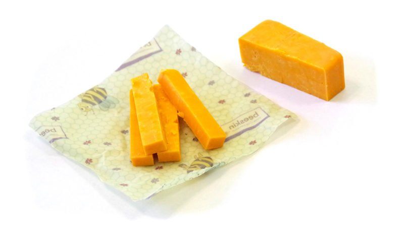 block of cheddar cheese cut into cubes and placed onto a beeskin size s in kids design
