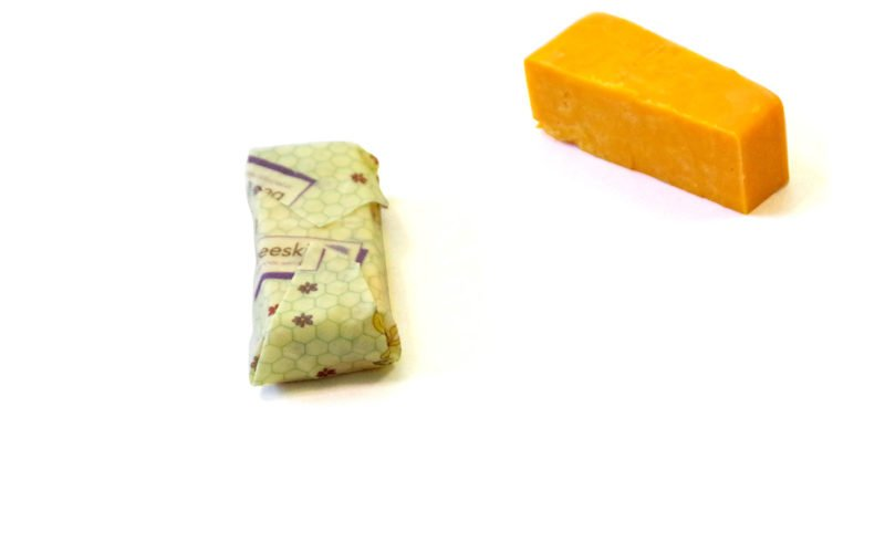 block of cheddar cheese cut into cubes and placed onto a beeskin size s in kids design, cut up cubes completely wrapped in beeskin